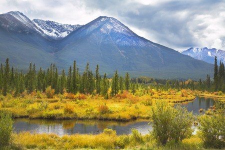 The picturesque bog surrounded by an autumn multi-coloured grass, on a background of ice mountains of the north