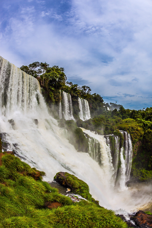 The concept of active and exotic tourism. The most famous waterfalls in the world - Iguazu. The waterfalls erupts clouds of water spray 免版税图像