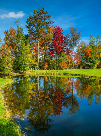 Golf Club on the road in French Canada. Concept of Golf tourism. Red, orange and yellow foliage is reflected to clear water of the lake