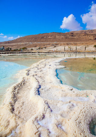 The concept of ecological and medical tourism. Reduced water in the salty Dead Sea, Israel. The evaporated salt has developed into fantastic patterns