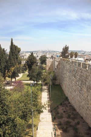 East Jerusalem from the walls surrounding the eternal city. Footpath through the park next to the historic walls 写真素材