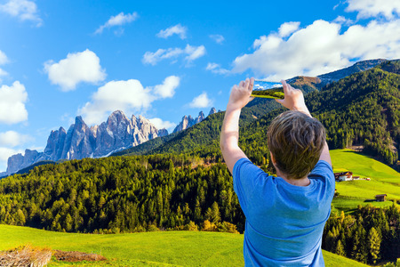 Beautiful landscape in the Dolomites. Charming boy in a blue T-shirt photographs the valley with a mobile phone. Wonderful day in South Tyrol. The concept of ecological and photo tourism Banco de Imagens