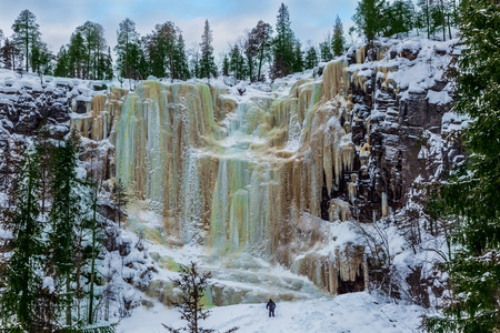 Man -  tourist in a blue jumpsuit climbs to frozen waterfall. Wall of frozen water. Multicolored icicles picturesquely fall off a steep cliff.  Lapland. The concept of photo and eco-tourism Фото со стока