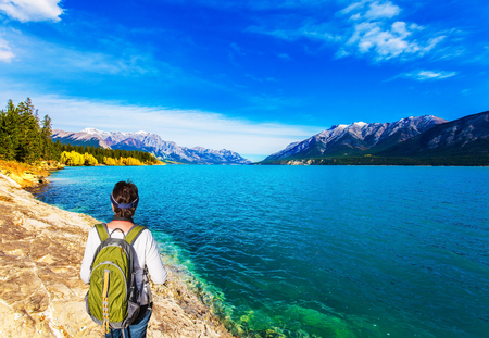 Abraham Lake in the Rocky Mountains of Canada. Middle-aged woman with a large green tourist backpack admires the lake. Concept of active, ecological and photo tourism