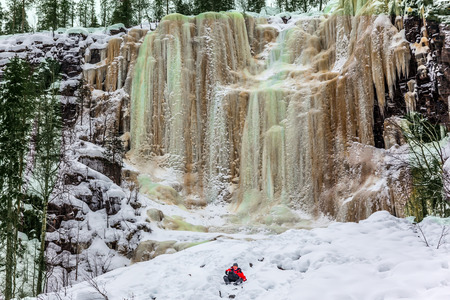 Happy hiker goes down in deep snow. Multicolored icicles of a frozen waterfall picturesquely fall off a steep cliff.  Lapland. The concept of photo and eco-tourism Фото со стока
