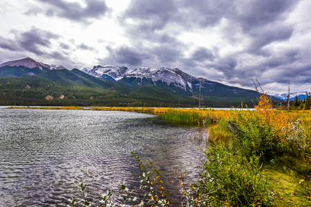 Autumn wind drives ripples in the dark water. The lakes, yellow autumn grass and mountains of Canada. The valley along the Pocahontas road. Concept of active and photo-tourism