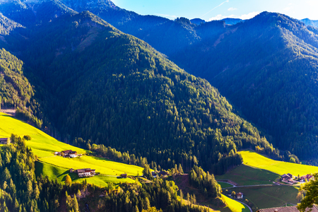 Delightful mountain valley in the Dolomites. Picturesque farms with red roofs are built on the slopes of the mountains. Wonderful day in South Tyrol. The concept of ecological and photo tourism Stock Photo