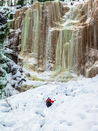 Happy hiker goes down in deep snow. The frozen waterfall picturesquely fall off a steep cliff.  Lapland. The concept of active, photo and eco-tourism