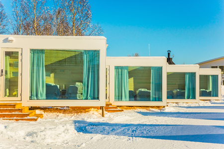 ROVANIEMI, LAPLAND, FINLAND - MARCH 7, 2017. Magnificent hotel in Lapland. Crouching road in winter frosty day. Concept of active tourism