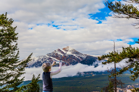 Boy with blond hair photographs landscape with a mobile phone. Rocky Mountains, Canada. Pyramid Mountain glistens in the sun over morning fog. The concept of ecological and photo tourism Archivio Fotografico