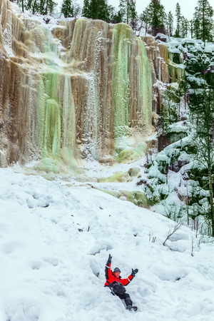 Happy tourist drives in deep snow. The frozen waterfall picturesquely fall off a steep cliff. Lapland. The concept of active, photo and eco-tourism