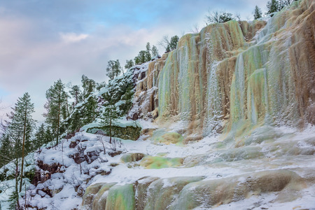 New Year in Lapland. Wall of frozen water. Multicolored icicles of a frozen waterfall picturesquely fall off a steep cliff.  The concept of photo and eco-tourism