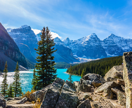Province of Alberta, Canadian Rockies. The cold sun is reflected in the icy water of the lake  Moraine. The concept of ecological, photographic and active tourism
