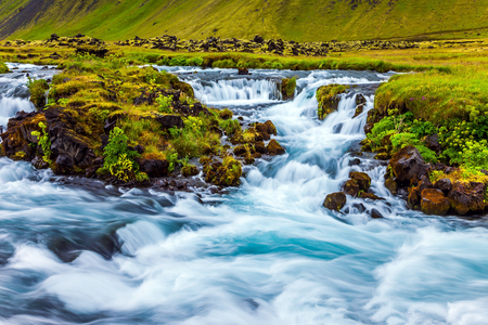 Powerful cascading waterfalls in Iceland. Wide picturesque valley along Highway 1 around the island. Travel in July. Concept of active and extreme tourism