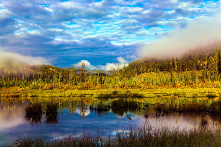 Rocky Mountains of Canada. Lake Patricia is surrounded by a spruce evergreen forest. Wonderful autumn landscape. The concept of active, ecological and photo tourism