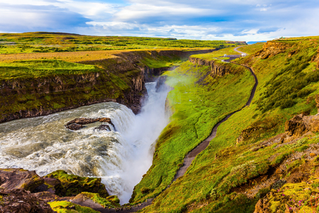 Fantastic Golden Waterfall Gulfoss in Iceland. Windy and sunny summer day. On the shore is a path for tourists. The concept of extreme and phototourism Banco de Imagens