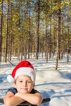 Frosty winter day in the Arctic. Lapland. The snow-covered coniferous forest. Handsome boy in red Santa Claus hat smiling. The concept of extreme and active tourism