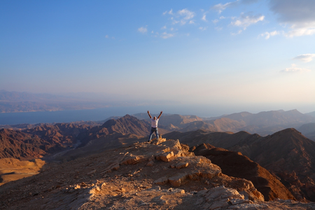 Classical bible landscape - desert Sinai in a morning fog, Red sea and the lonely tourist Banco de Imagens