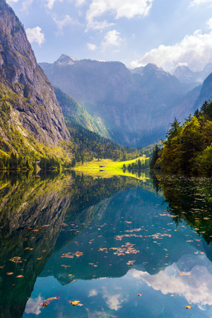 The slopes of the mountains are reflected in the lake water. Mountain Lake Koenigssee - the magical beauty of northern nature. The concept of active, ecological and phototourism