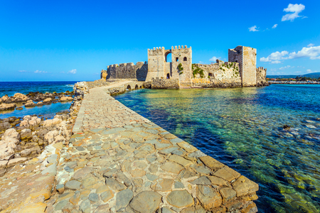 The picturesque ancient port in the Greek Mediterranean. Powerful walls and towers are made of hewn stones. Blue warm sea water is great for swimming.