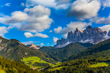 Picturesque farms with red roofs are built on the slopes of the mountains. Delightful mountain valley in the Dolomites, South Tyrol. The concept of ecological and photo tourism