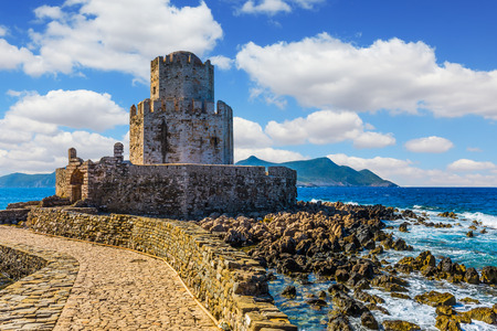 The fabulous three-tiered watchtower is built on long cape in the sea. Venetian fort castle Methoni. Seaside resort in Greece Mediterranean. The concept of active, photo and historical tourism