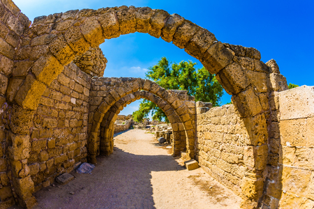 Sunny spring day. Israel.  Excursion to the Archaeological Park of the Roman Empire in ancient Caesarea. Concept of ecological and historical tourism. The remains of the covered arcades
