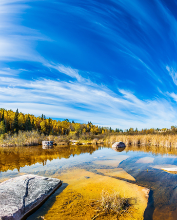 Indian summer in Manitoba, Canada. Winnipeg River, Old Pinawa Dam Park. The concept of ecological and recreational tourism. Incredible cirrus clouds