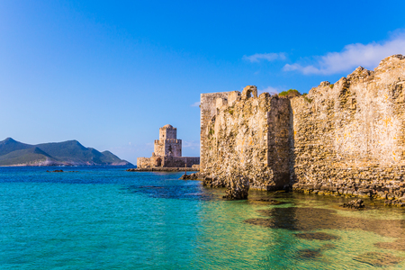 The magnificent three-tiered watchtower is built on long cape in the sea. The sea shoal beautiful azure color. Venetian fort castle Methoni on the Greek Peninsula Peloponnese. The concept of active, photo and historical tourism