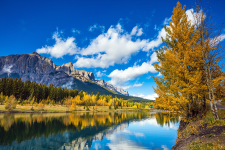 Concept hiking. The lake, mountains and red-orange trees. Bright shining day in the Canadian Rockies. Canmore, near Banff 免版税图像