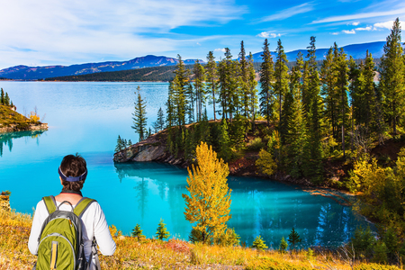 Middle-aged woman with a large tourist backpack admires the lake. Abraham Lake in the Rocky Mountains of Canada.Concept of active, ecological and photo tourism