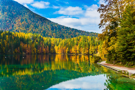 Scenic reflections of multicolored forests in the smooth water of the lake. Flood after rain. The quiet  Lago de Fusine, lake in Northern Italy. Concept of cultural and ecological tourism