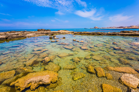 Flooded in the sea ruins and remains of port of King Herod in ancient Caesarea. Spring day in Israel. Израиль. Concept of ecological and archaeological tourism