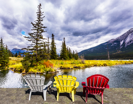 Rocky Mountains of Canada. Three comfortable multi-colored deck chairs stand by the lake. Cold wind drives a light wave in the water. Concept of ecological, active and photo-tourism