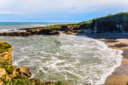 Powerful ocean surf. New Zealand. The picturesque Pacific coast of the South Island. Incredible journey to the ends of the world. The concept of ecological, active and photo tourism