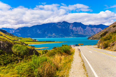 The concept of ecological, active and car tourism. South Island, New Zealand. Journey to the ends of the earth. Grassy mountains surround the Hawea Lake. The road around the lake