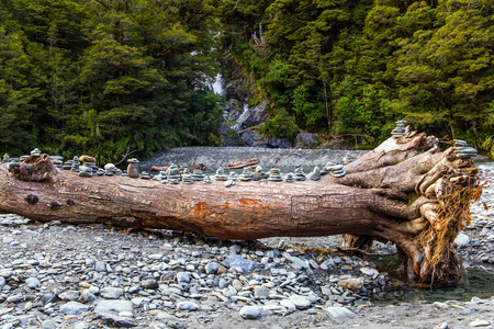 Picturesque dry snag and stone pyramids, folded by tourists. The picturesque fan-shaped waterfall Fantail. West Coast South Island, New Zealand. The concept of active, ecological and phototourism 版權商用圖片