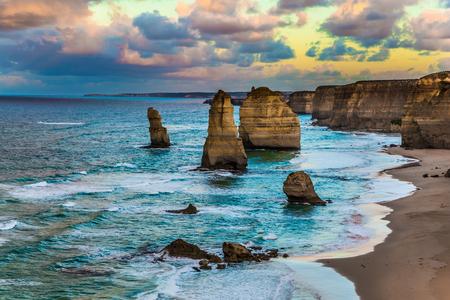 """Viaja a Australia. Temprano en la mañana en la orilla del mar. Nubes rosadas del amanecer sobre las famosas rocas """"Doce Apóstoles"""". El concepto de turismo activo, ecológico y fotográfico"""