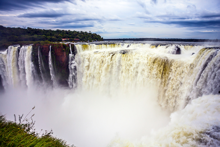 The most full-flowing waterfall in the world on the Parana River is the Garganta del Diablo. Grandiose waterfalls Iguazu in the rainy season. Concept of active and ecological tourism