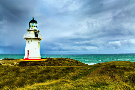 The South Island on a cloudy windy day. On the oceanfront is the famous white lighthouse Waipapa. Great trip to New Zealand. The concept of ecological, active and photo tourism