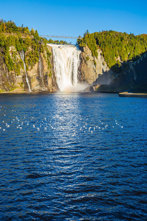 The blue lake and waterfall Montmorency in Montmorency Falls Park, in vicinities Quebec. Flock of water birds resting in water. The concept of active and cultural tourism 版權商用圖片