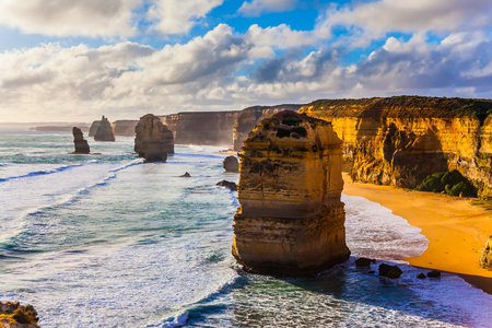 Rocks of the Twelve Apostles on grandiose coast of Australia. Powerful ocean surf at sunset. The concept of exotic and photo-tourism Stock Photo