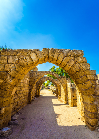 Sunny spring day. Arched passage - covered street of Port of Caesarea. Picturesque ruins of the ancient seaport Caesarea. Israel. Concept of ecological and historical tourism