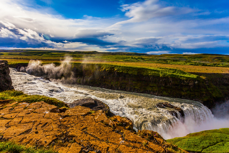 Gullfoss - Golden Waterfal on the Hvitau River. Cloudy and foggy July day in Iceland. The concept of extreme and phototourism