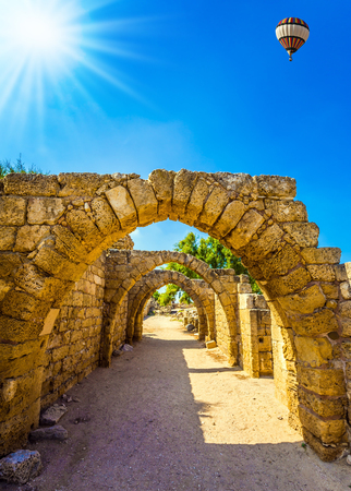 The remains of the covered arcades in Caesarea. Israel. Dazzling spring sun illuminates the ancient Mediterranean port. Concept of ecological and historical tourism