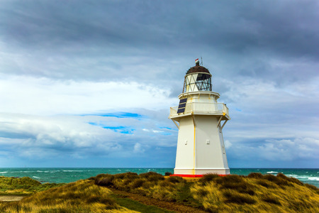 Independent trip to New Zealand. The snow-white lighthouse of Waipapa is visible on the horizon. Scenic South Island on a cloudy windy day. The concept of ecological, active and photo tourism