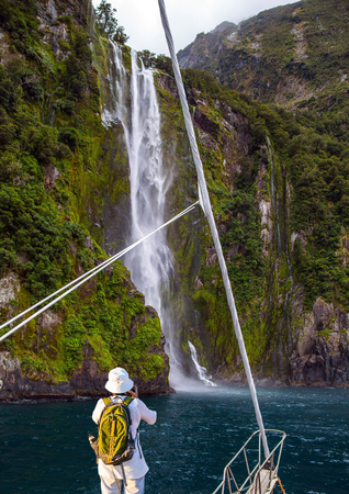 Woman with backpack in white hat photographs picturesque landscape. The waterfall crashes down from the cliff. New Zealand. boat trip on the Milford Sound fjord. Concept of exotic, active and photographic tourism