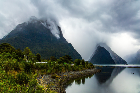 Magic country of fantastic heroes. New Zealand. Storm clouds cover the sky over the famous ocean fjord Milford Sound. Sunlight breaks through storm clouds. Concept of exotic, ecological and photographic tourism