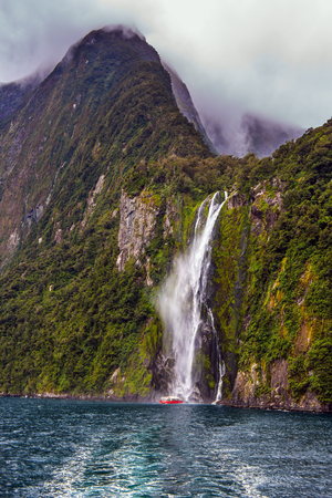 Magical journey to New Zealand. Tourist cruise aboard the Milford Sound fjord. Magnificent waterfall crashes down from the cliff. Concept of exotic, active and photographic tourism