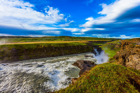 The falling water of the Golden Waterfall - Gullfoss roars. The wonderful summer day in Iceland. The concept of extreme and phototourism Stok Fotoğraf - 123371987